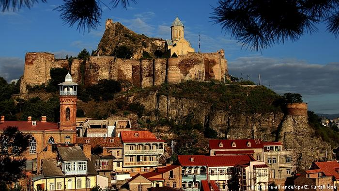 The downtown of the Georgian capital with old temple of Narikala is seen during sunrise in Tbilisi, Georgia. (picture-alliance/dpa/Z. Kurtsikidze)