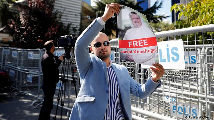 A protesters holds a sign saying: Free Jamal Khashoggi