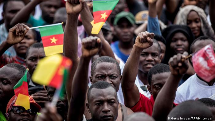 Supporters for the opposition party Movement for the Rebirth of Cameroon (MRC) hold a rally in Yaounde, holding their fists in the air. Some are waving small Cameroonian flags.