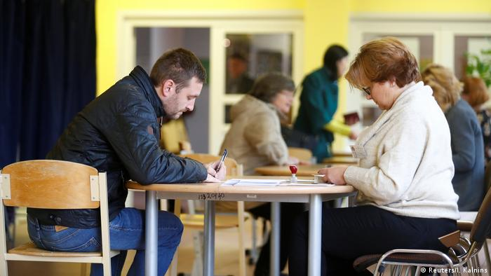 Voters filling out ballot papers in Latvia