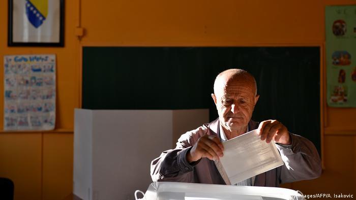 Stariji glasač ubacuje glasački listić u izbornu kutiju u Sarajevu
