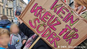 A protester holds up a sign reading: No cross (vote) for Söder) at a demonstration in Munich, Germany