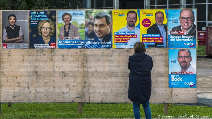A woman stands in front of a wall of campaign posters for the state election in Bavaria