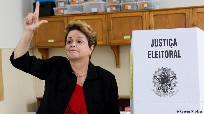 Dilma, em frente à cabine de votação, fazendo um L com a mão direita.