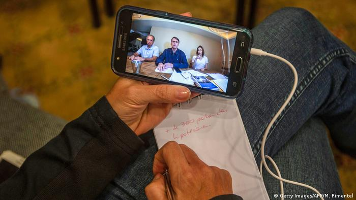 Foto de una persona que mira una publicación de Jair Bolsonaro.