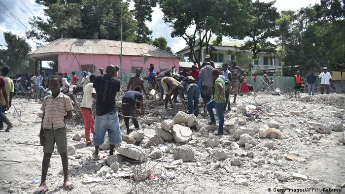 People standing in rubble in Gros Morne, Haiti