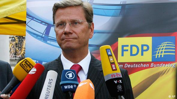 Guido Westerwelle surrounded by a host of microphones