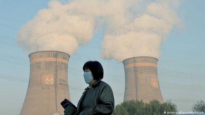 A woman wears a face mask near a coal power plant in Shenyang (picture-alliance/dpa/Mark)