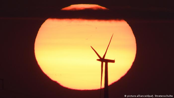 Modern electricity-producing windmill in Germany silhouetted against the sun (picture-alliance/dpa/J. Stratenschulte)