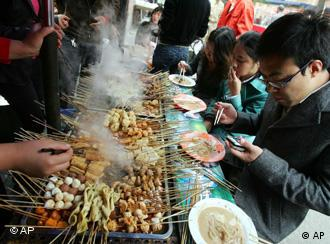 A large grill of food and Chinese people eating from it