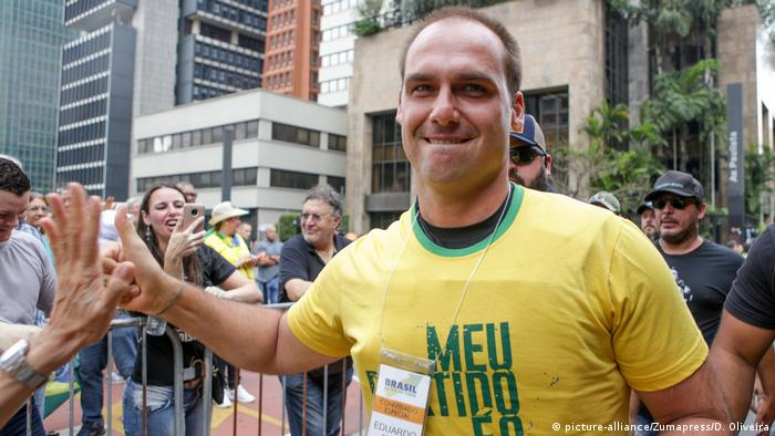 Eduardo Bolsonaro, in a bullet proof vest, high-fives supporters at a rally (picture-alliance/Zumapress/D. Oliveira)