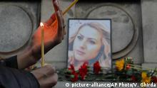 A woman holds a candle next to a portrait of slain television reporter Viktoria Marinova during a vigil at the Liberty Monument in Ruse, Bulgaria, Monday, Oct. 8, 2018. Bulgarian police are investigating the rape, beating and slaying of a female television reporter whose body was dumped near the Danube River after she reported on the possible misuse of European Union funds in Bulgaria (AP Photo/Vadim Ghirda)  