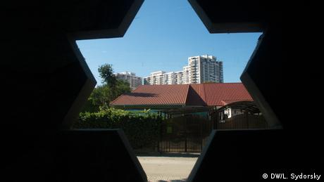 A high rise building is visible through a Star of David cutout (DW/L. Sydorsky)