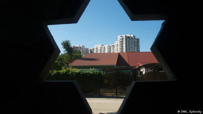 A high rise building is visible through a Star of David cutout