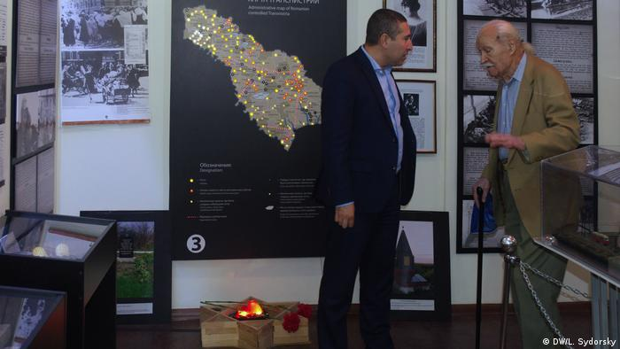 Kozlenko (left) speaks with Holocaust survivor Mihail Zaslavsky in front of a map showing the sites were Jews were executed
