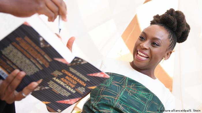 Jemand hält Adichie ihr Buch Americanah und einen Stift hin