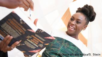 Chimamanda Ngozi Adichie smiles as someone requests a signature (picture-alliance/dpa/S. Stein)