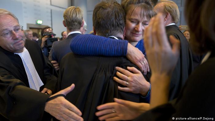 Members of the NGO Urgenda hug in a Netherlands courtroom