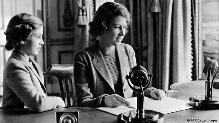 A princesa Elizabeth (futura rainha Elizabeth 2ª) e sua irmã, a princesa Margaret, em 1940: duas garotas em uma mesa com 2 microfones.