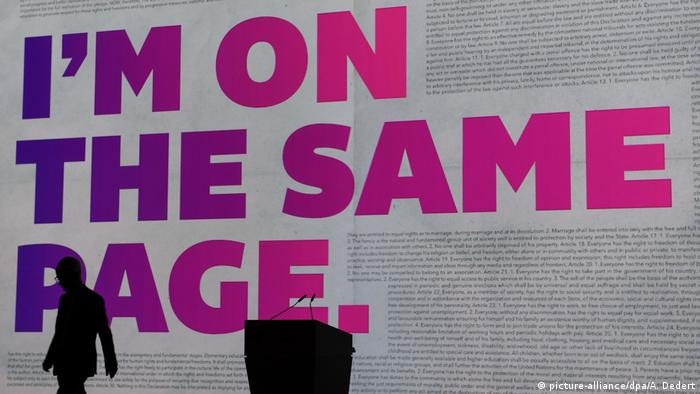 A shadow leaves the stage with the words 'I'm on the same page' in the background (picture-alliance/dpa/A. Dedert)