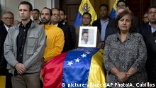 09.10.2018 Opposition leader Henrique Capriles, left, and lawmaker Dinorah Figuera, stand vigil around the flag-draped casket containing the remains of opposition activist Fernando Alban, during a solemn ceremony at the National Assembly headquarters, in Caracas, Venezuela, Tuesday, Oct. 9, 2018. International condemnation of Venezuela's leadership poured in Tuesday following the suspicious death of Alban authorities say evaded justice by throwing himself from the 10th floor of a police building. (AP Photo/Ariana Cubillos) |