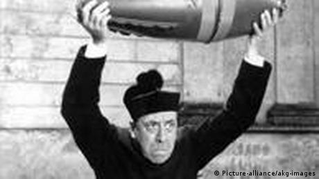 Film still, Don Camillo holds a bomb high over his head (Picture-alliance/akg-images)