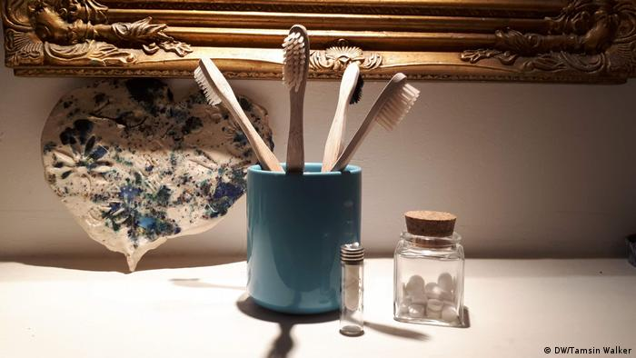 Pot containing bamboo toothbrushes, a jar of tooth tabs and dental floss