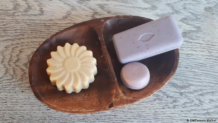Wooden dish with a bar of soap, shampoo and conditioner