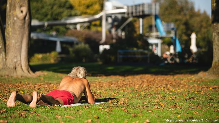 A person lying on a blanket in the grass near a public pool (picture-alliance/dpa/S. Gollnow)