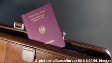 Ein Reisepass liegt auf einer Aktentasche