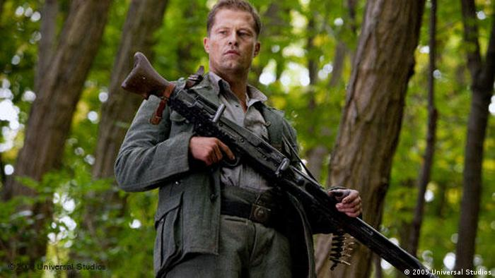 Til Schweiger wearing a gun in a forest in Inglourious Basterds by Quentin Tarantino (2009 Universal Studios)