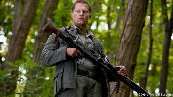 Til Schweiger wearing a gun in a forest in Inglourious Basterds by Quentin Tarantino (2009 Universal Studios)