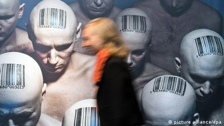 A woman walks past heads with bar codes on them (picture alliance/dpa)