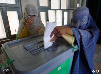 A veiled Afghan woman, right, casts her vote in the presidential election at a polling station in Kandahar province, south of Kabul