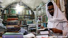 A religious student pages a book at the Howeish book market in the holy city of Najaf, 150 kilometres (95 miles) south of Baghdad, on August 16, 2018. - In the covered alleyways of old Najaf in Iraq, poetry and philosophy books compete with economic treatises, the Koran and other theological tomes for students' attention. (Photo by Haidar HAMDANI / AFP) (Photo credit should read HAIDAR HAMDANI/AFP/Getty Images)
