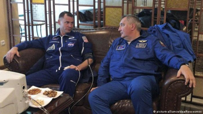 US astronaut Nick Hague (L) talks to the head of Roscomos Dmitry Rogozin (R)
