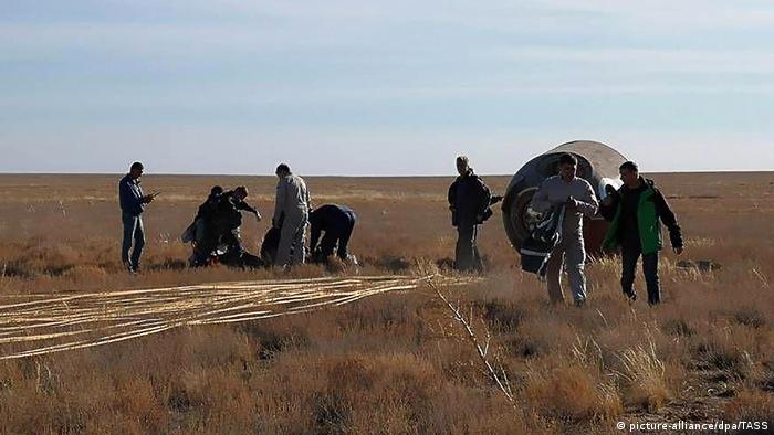 Rettungsmannschaften neben der notgelandeten russischen Sojus-Kapsel in der Steppe von Kasachstan