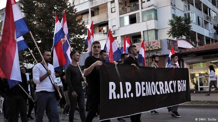 Mladi demonstranti nose hrvatske zastave i transparent R.I.P. DEMOCRACY BiH