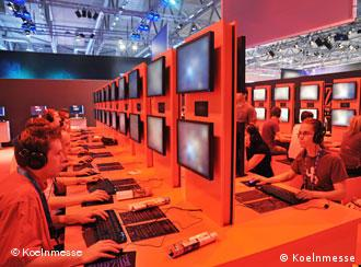 Gamers sit at rows of monitors and keyboards
