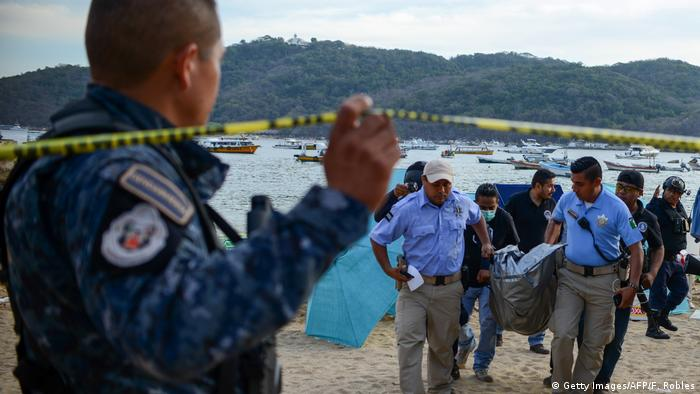 Police carry a dead body from an Acapulco beach