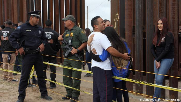 Members of a migrant family living in US and Mexico embrace each other during an event called Hugs not Walls