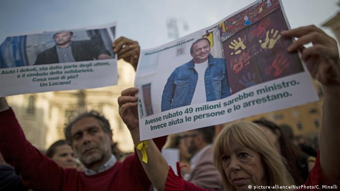 Protesters hold up placards in solidarity with Riace Mayor Domenico Lucano