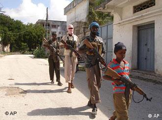 A young member of an Islamic militia group leads other fighters on patrol