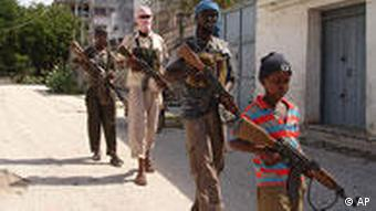 A young member of an Islamic militia group leads the way with other fighters as they patrol in southern Mogadishu
