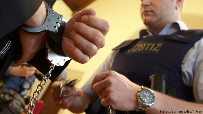 A police reaches towards a pair of handcuffed hands