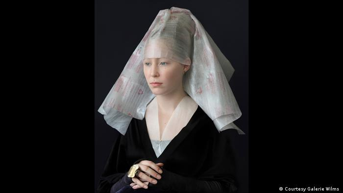 A photograph shows a woman dressed in a Flemish style but with clothing made of recycled materials (Courtesy Galerie Wilms )