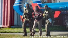 15.10.2018, Hamburg: Der Terror-Helfer Mounir el Motassadeq(M) wird von Polizeibeamten aus einem Hubschrauber am Geschäftsfliegerzentrum geführt. Nach fast 15 Jahren Haft ist der 9/11-Terrorhelfer Mounir el Motassadeq am Montag von einem Hubschrauber aus der Justizvollzugsanstalt Fuhlsbüttel abgeholt worden. Er soll in sein Heimatland Marokko abgeschoben werden. Foto: Daniel Bockwoldt/dpa - ACHTUNG: Person wurde aus persönlichkeitsrechtlichen Gründen gepixelt | Verwendung weltweit