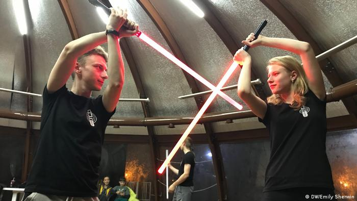 Daria and Vladimir lock light sabers during training at Moscow School of Saber Fighting