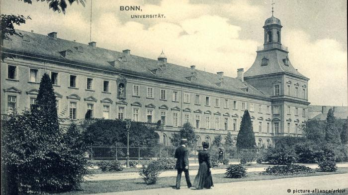 Historic view of the University of Bonn, a black and white photo with a man and woman strolling in front, apparently from the turn of the 20th century (picture-alliance/arkivi)