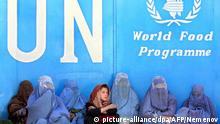 ARCHIV - Frauen sitzen vor dem Gebäude des UN-Welternährungsprogramms (WFP) in Kabul und warten auf die Verteilung von Lebensmitteln (Archivfoto vom 24.11.2001). Das UN-Welternährungsprogramms hatte seinerzeit eine Luftbrücke zur Versorgung der Hungernden in Afghanistan gestartet. Wegen drastisch gestiegener Nahrungsmittelpreise sind nach Angaben des Welternährungsprogramms der Vereinten Nationen (WFP) 2,5 Millionen Afghanen vom Hunger bedroht. Sie könnten sich nicht mehr selbst versorgen und seien «akut auf Nahrungsmittelhilfe angewiesen», teilte das WFP am Donnerstag (06.03.2008) in Kabul mit. Das WFP beginne daher noch in dieser Woche mit der Nothilfe für Hunderttausende Betroffene. (zu dpa 0491) +++(c) dpa - +++ |